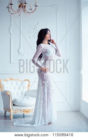 Perfect, sexy legs and ass of young woman wearing seductive white dress posing near luxury vintage c