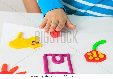 Child playing with clay molding shapes