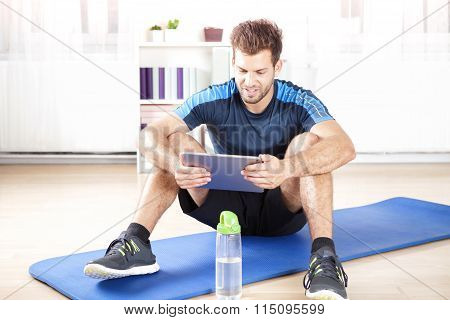 Fit Man Using His Tablet Computer After Exercise