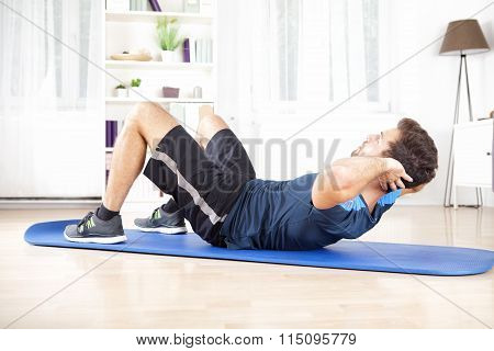 Athletic Man Doing Curl Ups Exercise At Home