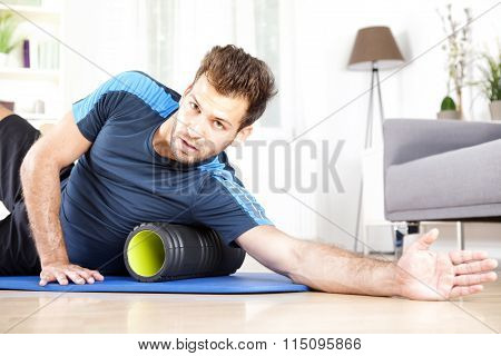 Handsome Guy Lying On Side With Foam Roller