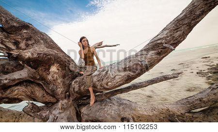 Pretty Woman Sitting On The Giant Roots.