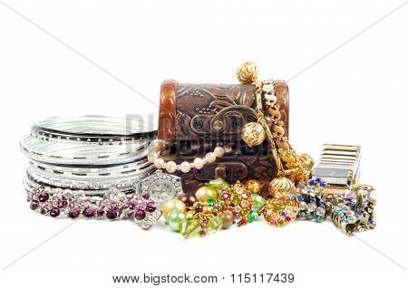 Accessory and gold jewelry in silver jewel chest, over white poster
