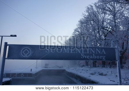 Suomenlinna fortress island sign on cold and foggy winter morning