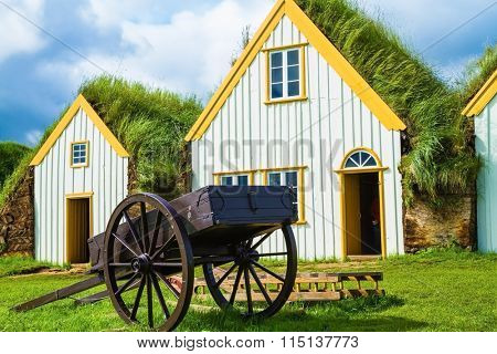 The ancient two-wheeled wooden cart on the front lawn. The village first settlers in Iceland. The reconstituted village - Pioneer Museum - Viking