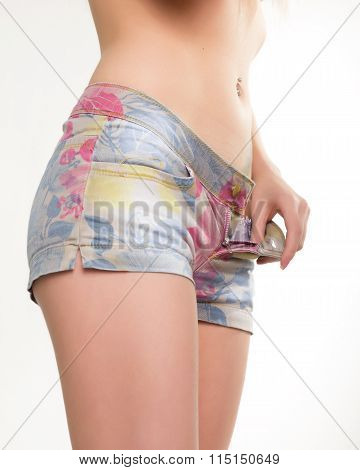 slim girl in colored denim shorts. she unzips shert