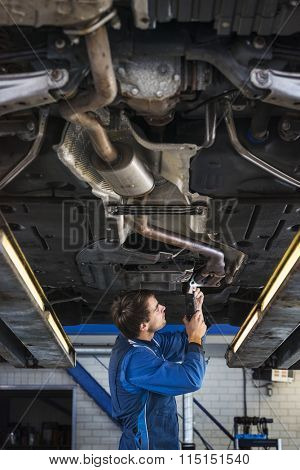 Mechanic underneath a car on a bride and fixing the exhaust