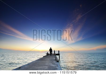 Jetty And Silhouette Of Angler Fishing During Sunset At Straits Of Malacca