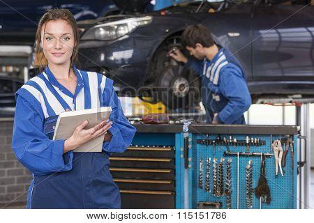 portrait of a female mechanic in a automotive workshop