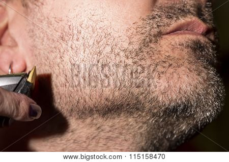 Hairdresser, cutting beard in her work place