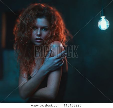 Young woman with red hair indoors portrait. Cold tint effect. Film style soft colors.