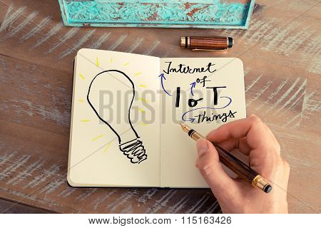 Woman Hand Drawing A Light Bulb On A Notebook