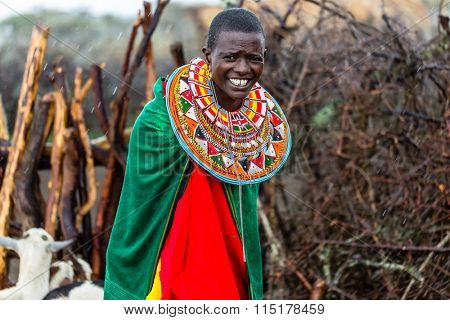 Massai woman standing in her village while it rains