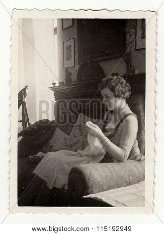 Vintage photo shows woman makes embroidery circa 1941.