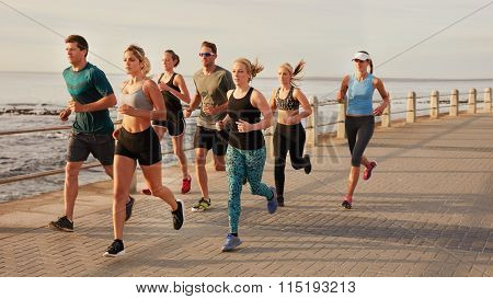 Young People Running Along Beach Boardwalk