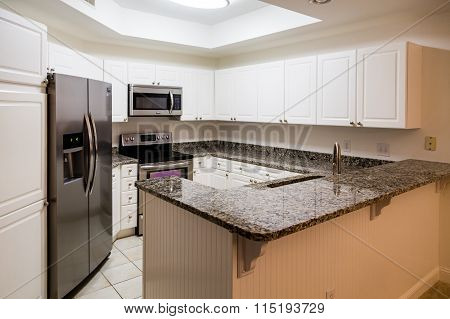 New stainless steel appliances and granite countertops with white wod cabinets poster