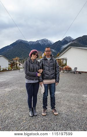 Couples Of Asian Man And Woman Wearing Winter Clothes  Standing In Front Of Snow Mountain In Matheso