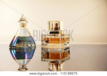 Two Bottles Perfume On Mirror Surface