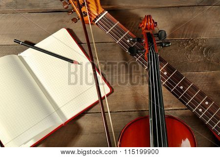 Electric guitar, violin, soprano saxophone and book on wooden background