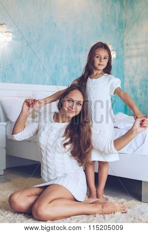 Mom with her 6 years old little daughter dressed in winter pajamas are relaxing and playing in the bed at the weekend together, lazy morning, warm and cozy scene. poster