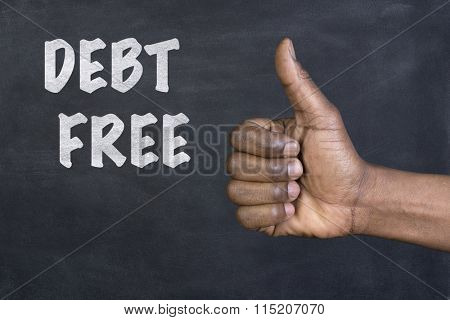 Male hand  giving the thumbs up gesture to the phrase Debt Free written on a blackboard