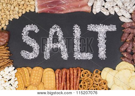 Word salt written with sea salt crystals surrounded by food containing a lot of salt