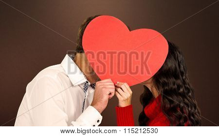 Couple covering faces with paper heart against shades of brown
