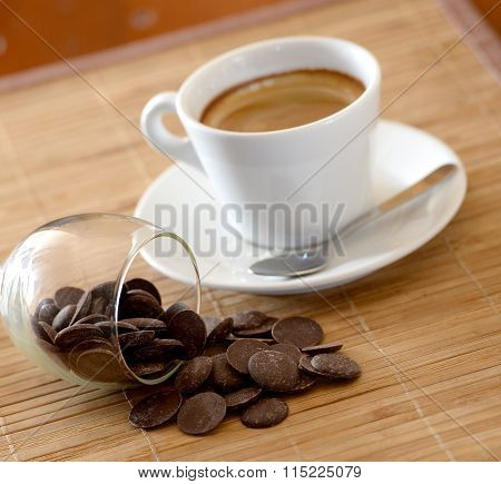 single coffee in a white cup near chocolate coins