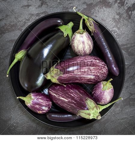 Eggplant varieties in black bowl over dark slate background.  Overhead view.