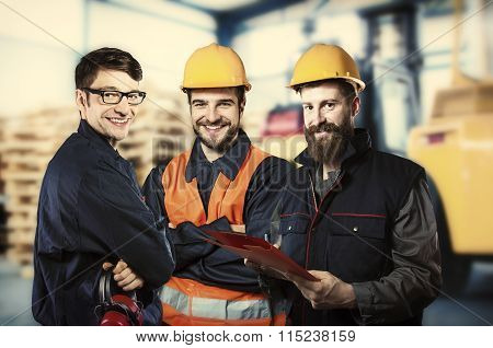 Smiling Workers In Front Of Forklift
