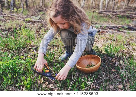 child girl exploring nature in early spring forest. Kids learning to love nature.