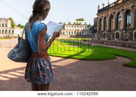 Young lady tourist standing in front of old building (Zwinger) in Dresden with guidebook
