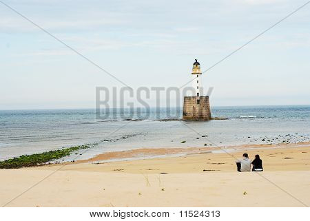 Lovers On A Beech With A Lighthouse