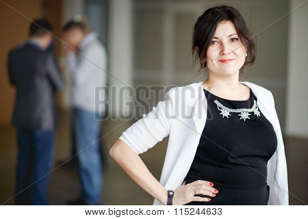 Successful attractive boss brunette with kind eyes stands inside office building and welcoming smile