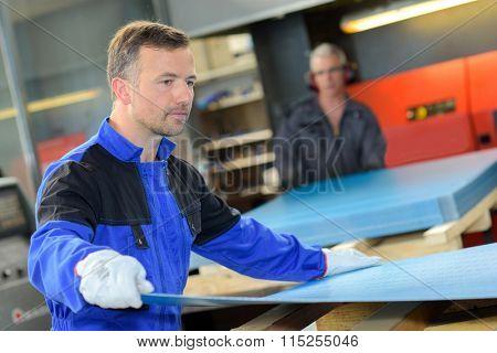 Workman holding sheet of metal poster