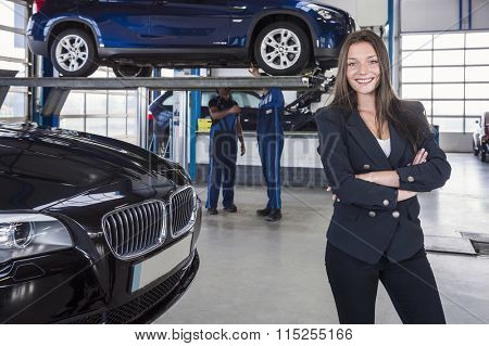 Happy customer in garage with her repaired car in the background