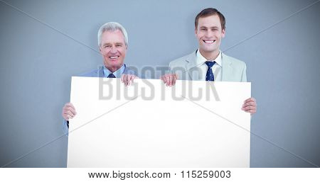 Smiling tradesmen holding blank sign against grey background