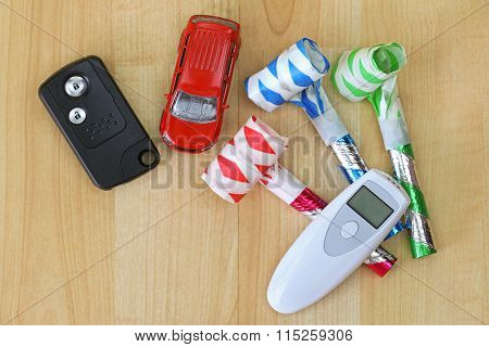 Digital alcohol breath tester device in white next to a car remote key and colorful party horns