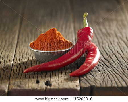 chili and chili powder on the wooden background