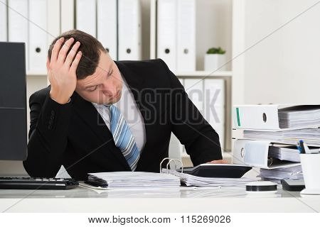 Stressed Accountant Sitting At Desk In Office