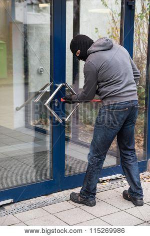 Man Using Crowbar To Open Glass Door