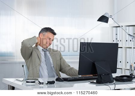 Businessman Suffering From Neck Pain At Desk
