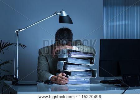 Businessman Leaning Head On Binders While Working Late