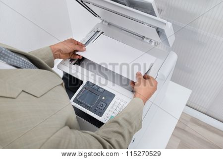 Businessman Keeping Paper On Photocopy Machine