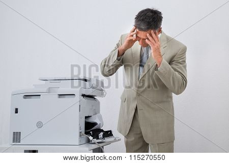 Businessman Looking At Paper Stuck In Printer