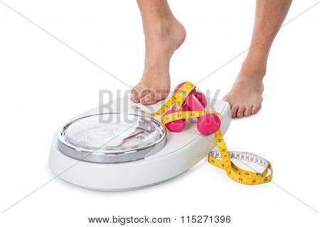 Woman Stepping On Weight Scale With Dumbbells And Tape Measure