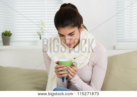 Sad Woman Holding Tee Mug On Sofa At Home