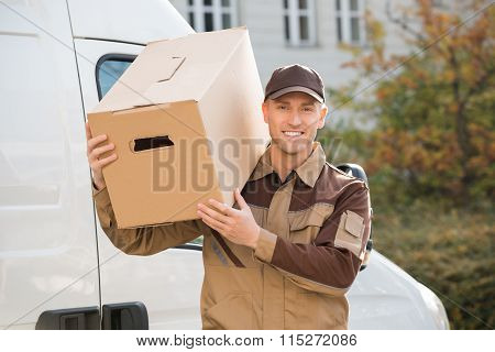 Delivery Man Carrying Cardboard Box On Shoulder