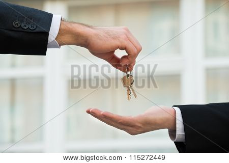 Real Estate Agent Giving House Keys To Businessman
