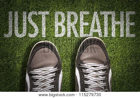 Top View of Sneakers on the grass with the text: Just Breathe